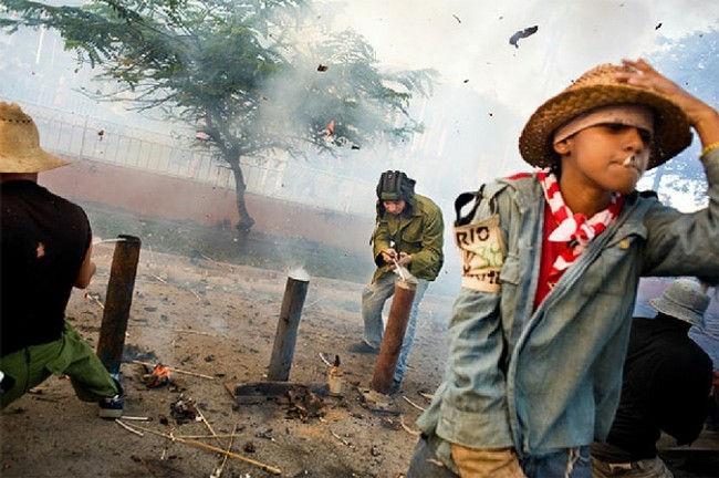 """Похвальная грамота в категории «Люди»: Без названия, Фаусто Подавини, Италия. Фотография был снята в Сан-Хуан-де-лос-Ремедиос, Куба, во время празднования """"Las Parrandas"""", в котором используются фейерверки. Дети зажгли фейерверки и бегут"""