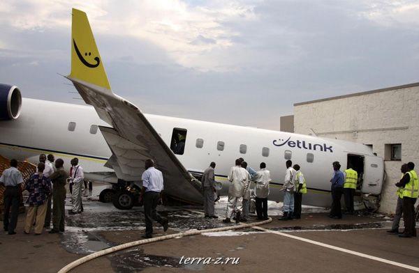 Официальные лица Руанды осматривают самолет Jetlink, который врезался в VIP-зал в аэропорту Кигали 12 ноября 2009. REUTERS/Hereward Holland