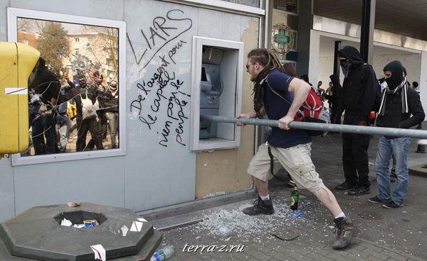 Протестанты крушат банкомат во время антиНАТОвской демонстрации в пригороде Страсбурга. 4 апреля 2009. REUTERS/Vincent Kessler
