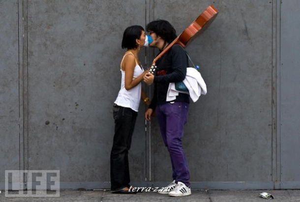 Влюбленная парочка целуется через защитные маски во время эпидемии вируса H1N1 в Мехико.