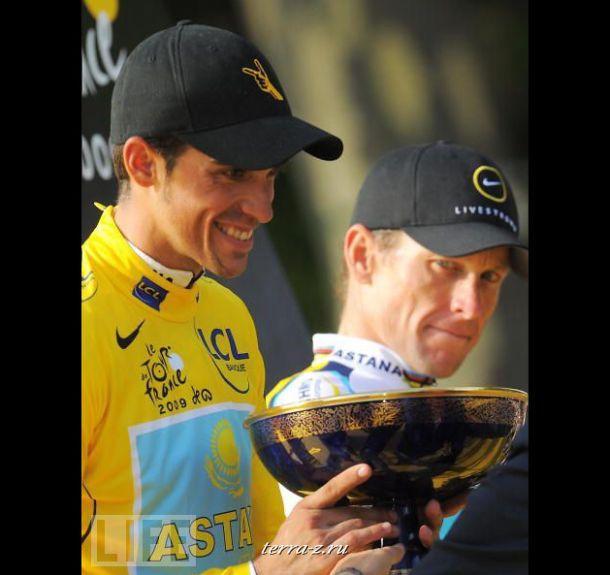 Победитель Tour de France 2009 испанец Альберто Контадор держит кубок победителя под пристальным взглядом семикратного обладателя титула чемпиона Ланса Армстронга.