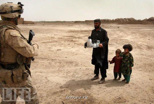 Житель Афганистана с маленькими дочерьми встречает американского военного чашкой чая. Военнослужащие США в этот период налаживали отношения с мирным населением, чтобы узнать информацию о возможных атаках талибов.