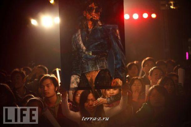 Поклонница Майкла Джексона держит в руках плакат с изображением своего кумира на пекинской премьере фильма This is It о последних днях певца и репетициях его финального тура.