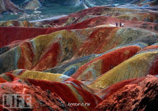 Туристы гуляют по разноцветным холмам китайского геопарка Занжи.
