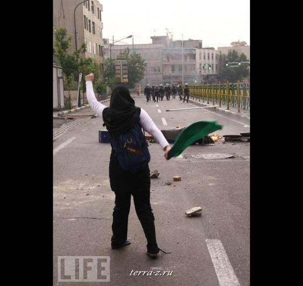 Одинокая демонстрантка угрожает иранской полиции в Тегеране после того, как Махмуд Ахмадинежад объявил себя победителем на президентских выборах. В течение июня вся страна была потрясена волной демонстраций против беспредела полиции.
