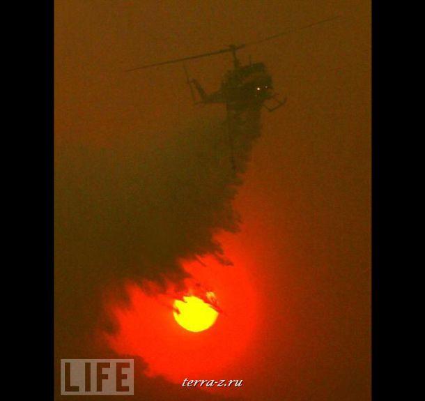 Вертолет распыляет воду над районами Калифорнии, где в августе этого года из-за пожаров сгорело несколько десятков тысяч километров территории и были эвакуированы жители 10 тысяч домов.