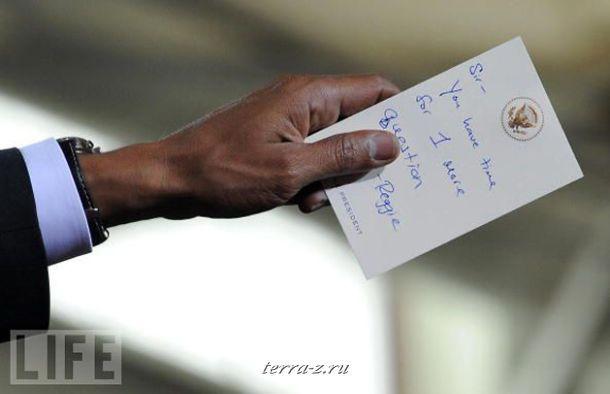 Президент США Обама держит записку от своего ассистента Реджи Лава во время выступления по вопросам медицинского страхования в Портсмуте, Нью-Гемпшир.