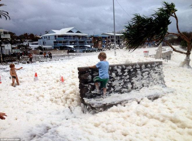 Экстремальные погодные условия, которыми омрачена Австралия в последние недели, приняли сегодня неожиданный поворот. Десятки пляжных городов оказались погруженными в морскую пену, высота которой достигала отметки 1,2 метра. Уникальное явление подарило целое море наслаждения сотням детей, которые играли в бесконечной пенной ванне. Несмотря на то, что в целом циклон Освальда принес много несчастий австралийцам, последние происшествия имели следствием позитивные эмоции, поскольку такое случается крайне редко в мире. Волна за волной накатывали на берег, заполняя все пространство вокруг пеной, смешанной с пылью и грязью. В пене оказались не только прибережная зона, но и кварталы, довольно отдаленные от океана. Для образования пены в таких невероятных количествах необходимо сочетание несколько условий, таких как мощные волны, гроза и сильный ветер. Но даже сочетание этих природных явлений не дает гарантии обильного пенообразования. Пена – только часть, хотя и довольно приятная, циклона Освальда. В основном австралийские города страдают от наводнения, которое поглотило уже многие населенные пункты штата Квинсленд. Люди покидают свои дома в поисках более безопасных мест: «Лучше уйти из дома сегодня, чем рисковать жизнью завтра». Циклон будет продолжать свою черную работу еще как минимум до середины следующей недели ,поэтому те, кто покинул свои дома, обречены на длительное пребывание в наскоро организованных лагерях для беженцев, которые расположены в школах, спортзалах, крытых стадионах. Источник: www.dailymail.co.uk