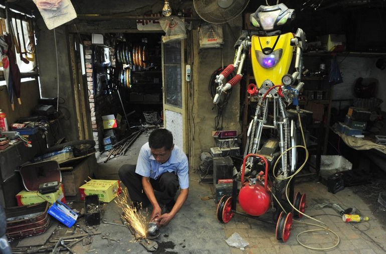 a-49-year-old-electric-bike-mechanic-who-identified-himself-only-as-wu-welds-a-component-to-fit-onto-his-newly-made-robot-r-at-his-repair-shop-in-shenyang-liaoning-province-june-