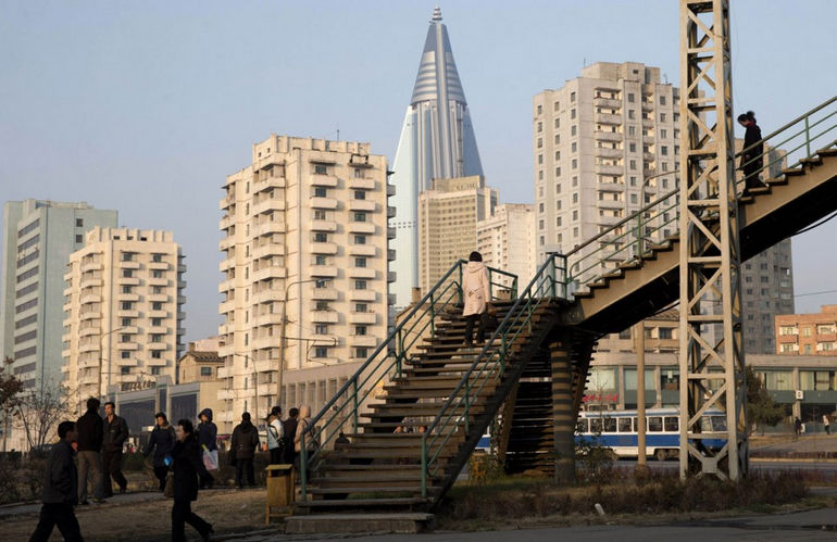 The-105-story-Ryugyong-Hotel-which-remains-under-construction-stands-over-residential-buildings-in-Pyongyang-on-November-19-2012.-AP-PhotoNg-Han-Guan-960x622