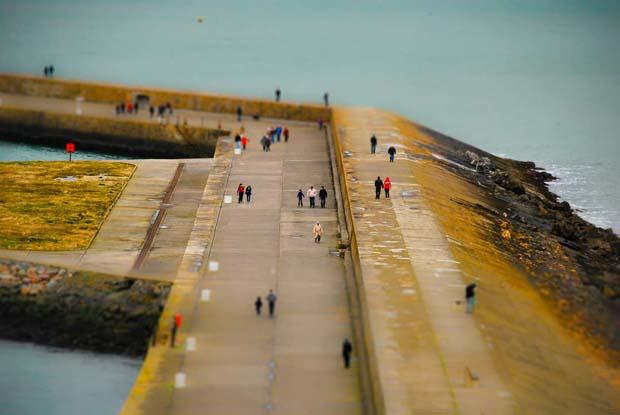 Тилт шифт эффект: Люди прогуливаются по набережной.